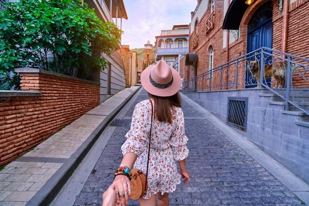 Следуй за мной концепции и путешествуй вместе. девушка-путешественница в шляпе и коротком комбинезоне держит парня за руку и гуляет по европейскому городу
