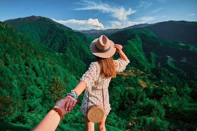 Следуй за мной концепции и путешествуй вместе. девушка-путешественница в шляпе, круглой соломенной сумке и коротком комбинезоне держит парня за руку и ведет к отпуску в зеленых горах.