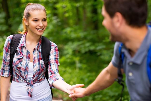 Подписывайтесь на меня! счастливая молодая влюбленная пара с рюкзаками и держась за руки во время прогулки по лесу
