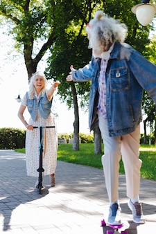 フォローしてください。スケートをしながら妻に手を差し伸べる素敵なポジティブな男