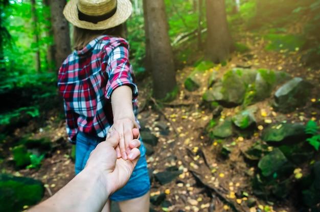 나를 따라 산에서 사진. 체크 무늬 셔츠와 밀짚 모자에 세련 된 여자. 방황 개념. 커플 하이킹과 여름 여행. 자연에서 손을 잡고.