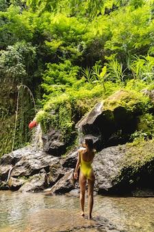 フォローしてください。緑の木々を楽しみながらエキゾチックな自然を楽しんでいるかなりブルネットの女性