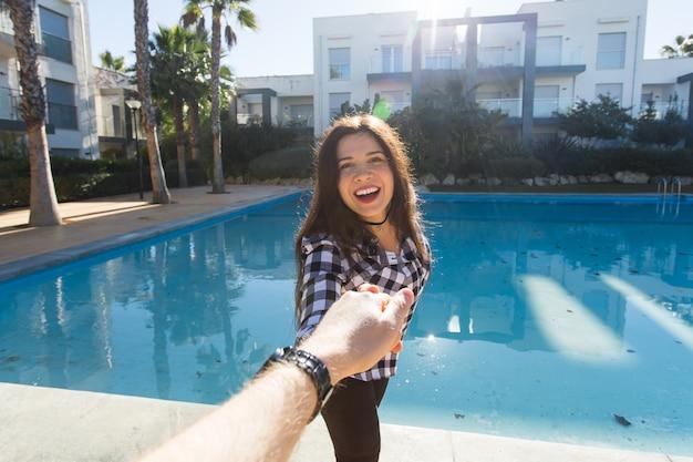 フォローしてください。休暇の概念。スイミングプールの近くのリゾートで彼氏の手を握って幸せな若い女性。
