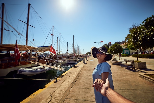 フォローしてください。豪華なヨットで港の近くに立っている帽子をかぶった若い幸せな女性。トルコの旅行と休暇の概念