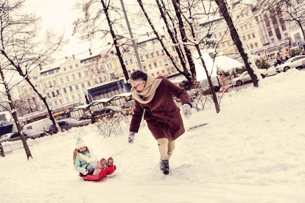 우리의 예를 따르십시오. 썰매에 앉아 농담에서 웃 고 귀여운 소녀