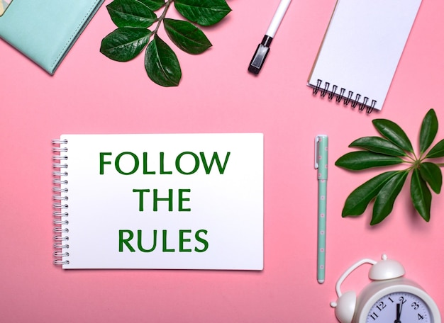 Follow the rules is written in green on a white notepad on a pink background surrounded by notepads, pens, white alarm clock and green leaves. educational concept