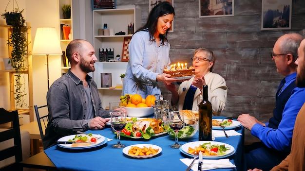 家族の夕食で彼女の夫のためにバースデーケーキで妻のショットに従ってください。