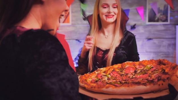 ハロウィーンパーティーでピザを持って到着する魔女の女の子のショットをフォローしてください。