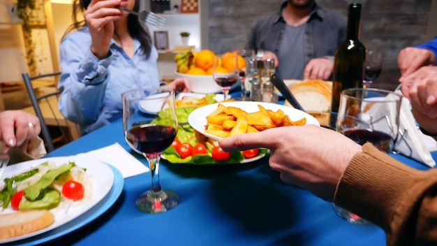 家族の夕食で彼の妹にジャガイモを提供している若い男のショットに従ってください。