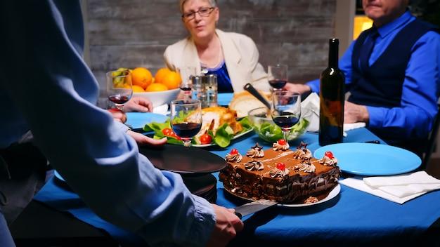 家族の夕食で母親にケーキのスライスを与える若い女性のショットに従ってください。