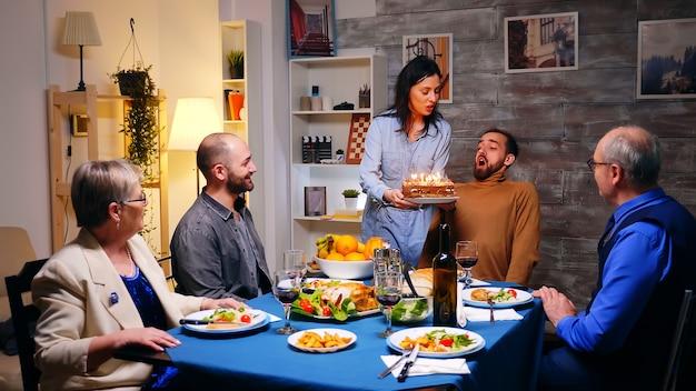 家族の夕食で彼女の兄弟のためにバースデーケーキで若い女性のショットに従ってください。