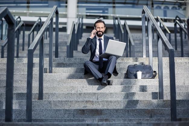 ファローアップ。階段に座って電話で会話をしている楽観的なプロのビジネスマン