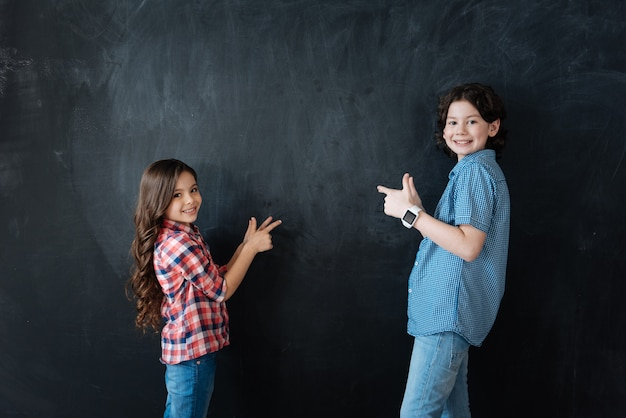 Follow us . friendly optimistic delightful children standing in blackboard and enjoying imaginary drawing while holdig thumbs up