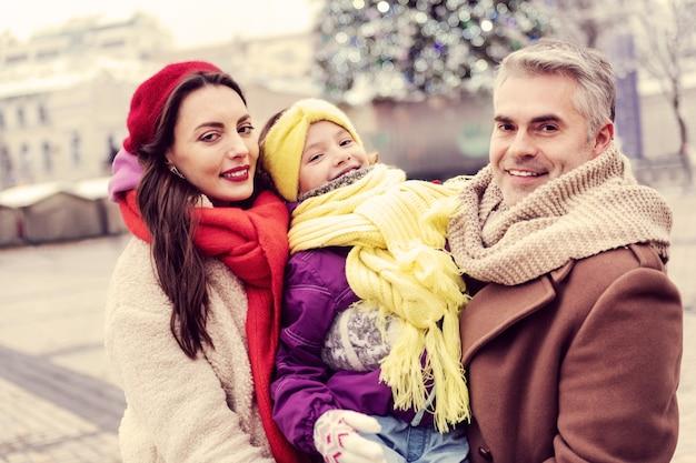 우리를 따르십시오. 함께 걷는 동안 그녀의 가족 근처에 서있는 예쁜 젊은 여자