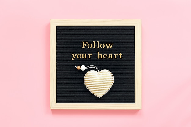Follow your heart. motivational quote in gold letters and decorative textile heart on black letter board on pink background.