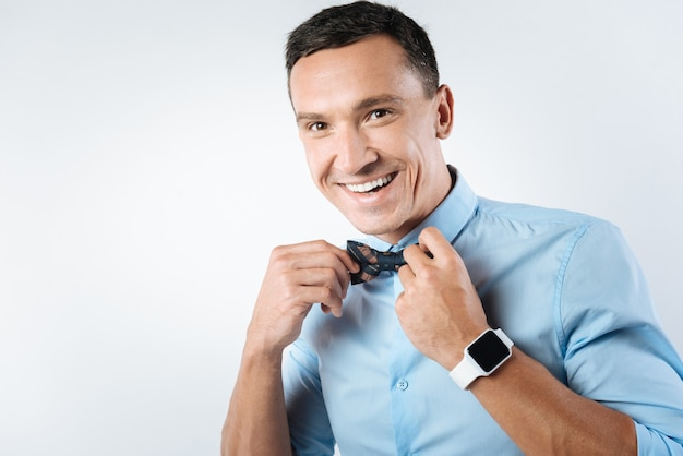 Following fashion. cheerful positive handsome man smiling and trying to be stylish while fixing his bow tie