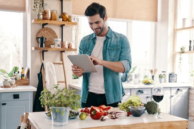 次のレシピ。デジタルタブレットを使用して、自宅のキッチンに立って笑っているカジュアルウェアのハンサムな若い男