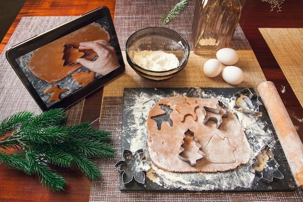 디지털 태블릿의 레시피에 따라 - 크리스마스 진저브레드를 만들기 위한 틀을 사용하여 반죽을 잘라냅니다.