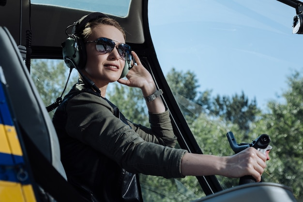 Fond of flying. the close up of a charming young woman sitting in the pilot booth of a helicopter and posing for the camera