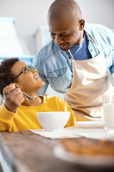 С любовью смотрю. приятный молодой человек в фартуке разговаривает со своим сыном и нежно улыбается ему, пока он ест хлопья на завтрак