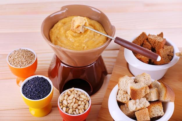 퐁듀, 나무 표면에 커팅 보드에 향신료, 러스크 및 비스킷의 작은 그릇