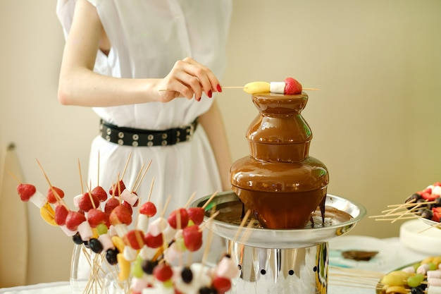 Fondue with a chocolate fountain and sweets for it.sweet theme.