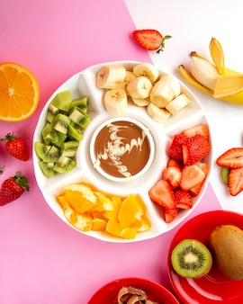 Fondue with chocolate kiwi strawberry banana and orange