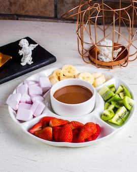 テーブルの上の果物とフォンデュ