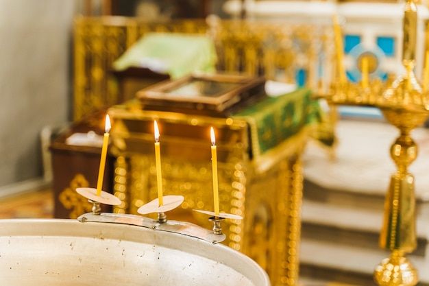 Font and 3 burning candles with water in church for epiphany