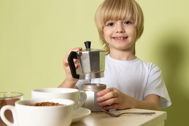 Un ragazzo sorridente felice di vista della fonte che prepara la bevanda del caffè sulla tavola sul pavimento colorato pietra