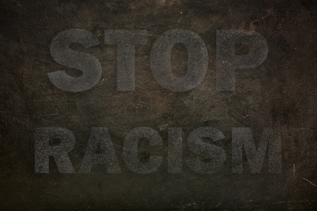 Font with transparency stop racism graffiti on a black stone background