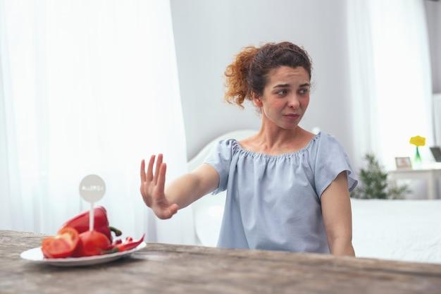 代替食品。彼女のアレルギーを引き起こしているトマトとコショウを置き換えるための代替食品オプションを探している思春期の女性