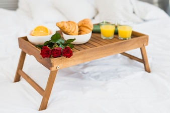 Food and blooms on breakfast table on bed