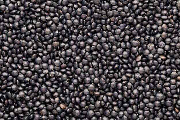 健康な乾燥黒レンズ豆の食品と料理の背景。