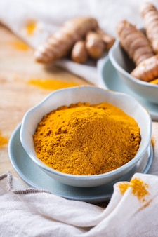 食べ物や飲み物、ダイエット栄養、ヘルスケアの概念。生の有機オレンジウコンの根と粉末、調理台の上のクルクマロンガ。インドの東洋の低コレステロールスパイス。