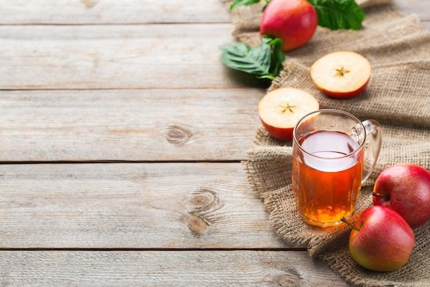 食べ物や飲み物、収穫秋秋のコンセプト。素朴な木製の背景に熟した果実とマグカップで新鮮な有機リンゴジュース。コピースペース