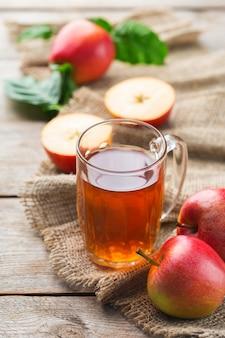 食べ物や飲み物、収穫秋秋のコンセプト。素朴な木製の背景に熟した果物とマグカップで新鮮な有機リンゴジュース