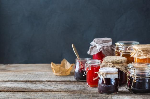 음식과 음료, 수확 여름 가을 개념. 나무 테이블에 있는 항아리에 다양한 계절 딸기와 과일 잼. 복사 공간 소박한 배경