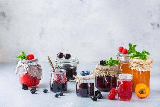 Еда и напитки, концепция сбора урожая летом и осенью. ассортимент сезонных ягод и фруктовых джемов в банках на деревянном столе. копировать космический деревенский фон