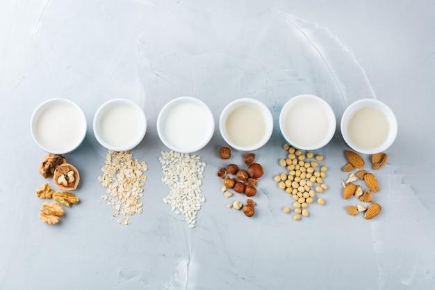 食べ物や飲み物、ヘルスケア、ダイエット、栄養の概念。台所のテーブルの上のグラスのナッツからの有機ビーガン非乳製品ミルクの品揃え。上面図フラットレイ背景