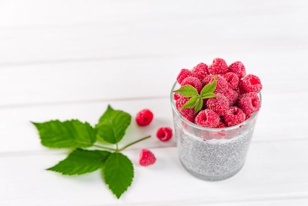 Еда и напитки, здоровое питание и концепция диеты. домашний белый пудинг чиа со свежими ягодами и зелеными листьями на завтрак на светлом кухонном столе.