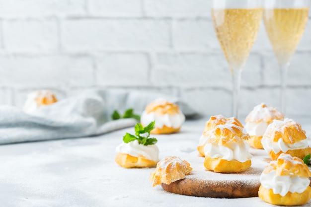 Еда и напитки, концепция праздников. вкусные сладкие домашние профитроли со сливками и бокалами шампанского на современном кухонном столе