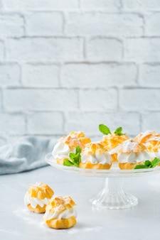 Еда и напитки, концепция праздников. вкусные сладкие домашние профитроли со сливками на современном кухонном столе. скопируйте космический фон