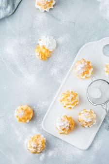 Еда и напитки, концепция праздников. вкусные сладкие домашние профитроли со сливками на современном кухонном столе