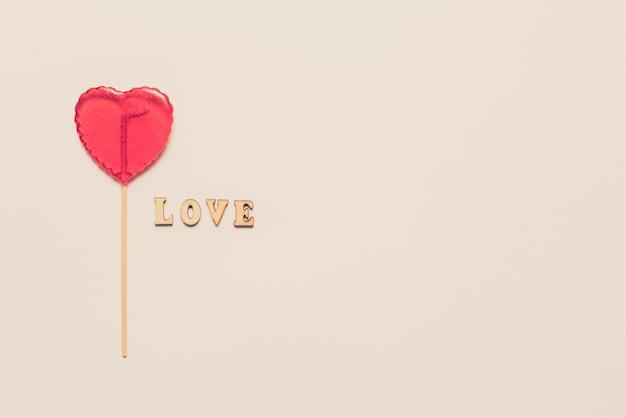 Еда и напитки, концепция праздников. леденец на палочке в форме сердца для любви день святого валентина с белым фоном. копировать пространство