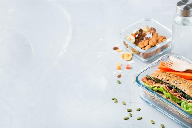 Еда и напитки, натюрморт, диета и питание, здоровое питание, концепция на вынос. ланч-бокс с бутербродом, фруктами, овощами, ореховой смесью и бутылкой воды. скопируйте космический фон