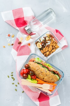 Еда и напитки, натюрморт, диета и питание, здоровое питание, концепция на вынос. ланч-бокс с бутербродом, фруктами, овощами, ореховой смесью и бутылкой воды. плоский фон вид сверху