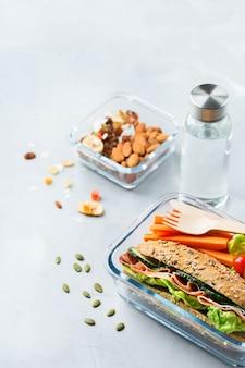 음식과 음료, 정물, 다이어트와 영양, 건강한 식생활, 개념을 없애십시오. 샌드위치, 과일, 야채, 견과류 믹스, 물 한 병이 포함된 도시락