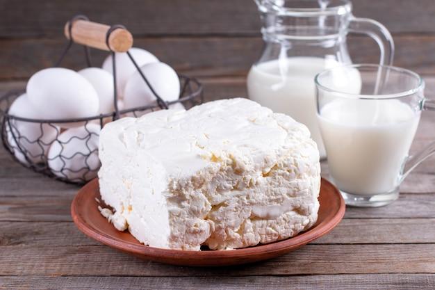 食べ物と食事のコンセプト-カッテージチーズ、牛乳の水差し、牛乳のガラスと木製のテーブルの上の鶏卵のクローズアップ