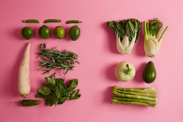 Еда и свежие овощи. зеленая спаржа, лайм, авокадо, белый редис, rosemay, базилик, изолированные на розовой поверхности. продукты или ингредиенты для приготовления здоровых блюд из органических продуктов. диета, сельское хозяйство